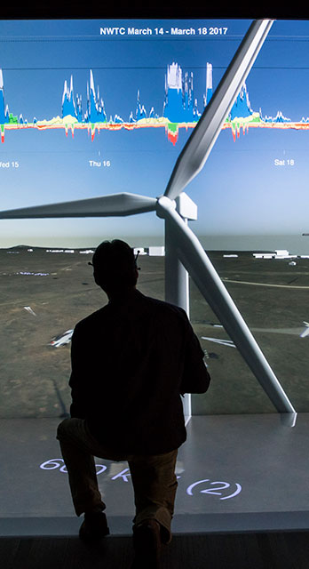 A man crouches looking at a visualization of a wind turbine.