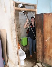 Researcher using a vacuum to trap mosquitoes in a bathroom
