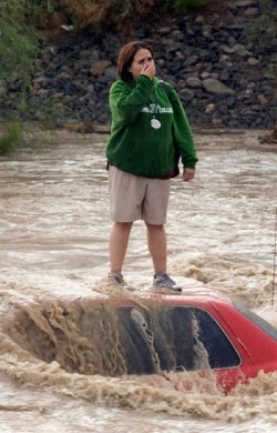 A freightened woman stands on top of her car, which has been mostlyi submerged by a flosh flood