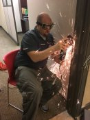 Nick Tinsley grinding a door for access control installation