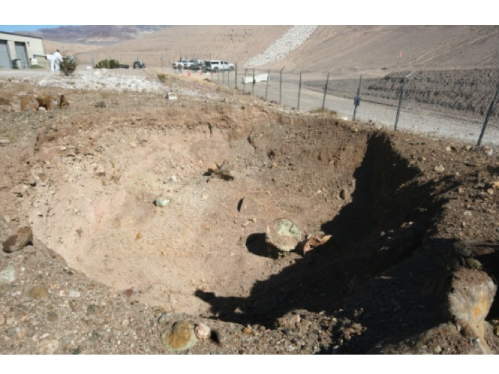Figur 4: Der Krater aus der Nähe und Fassüberreste (gemäss Photo Nr. 2 vom 21. Oktober 2015, Anhang II-6, Nevada Department of Public Safety [2015]: Report on the October 18, 2015 industrial fire incident at the closed state of Nevada low-level radioactive waste site, State Fire Marshal Division, December 30, 2015)
