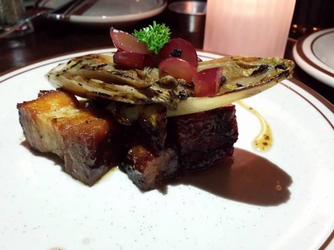 Flanc de porc, endives grillées, raisins marinés et moutarde à l'érable