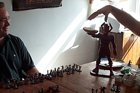 Two men sit at a table. Small plastic HeroClix figures stand arrayed on a large wooden table while a much larger comic book figure (Galactus) holds a bagel.