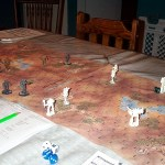 Grey and white robot-like figurines battle on a hexagonal map. The lower left corner of the photo shows a rulebook and some dice.
