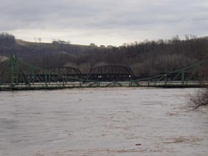A river hits the bottom of a large bridge.