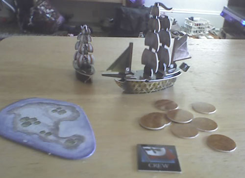 "Two small pirate ships, constructed from plastic components, ""sail"" on a table. An island appears to the left; a number of gold tokens representing treasure appears to the right."