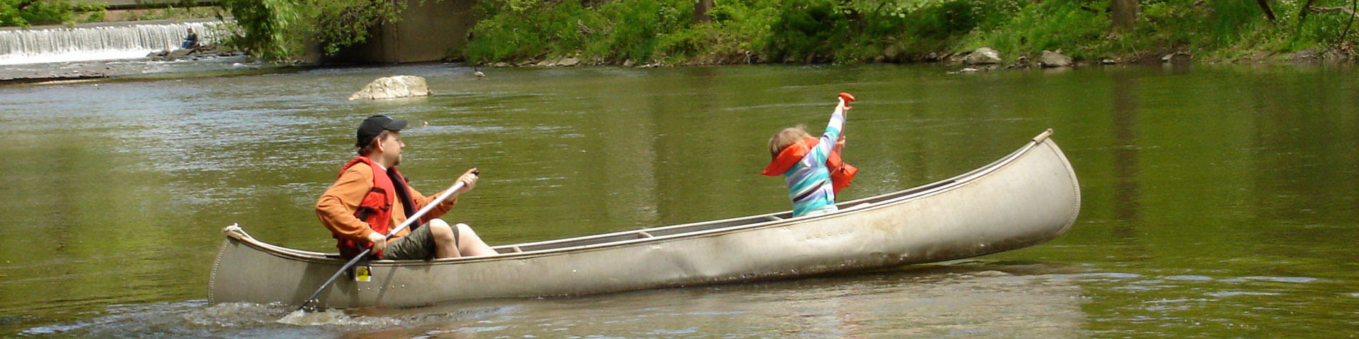 An adult male and a young girl paddle in a canoe on a creek.