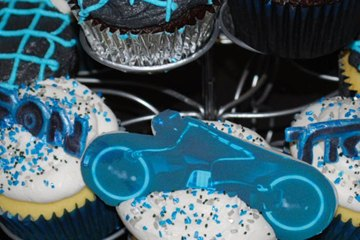 A pyramid of chocolate and vanilla cupcakes decorated with blue grids. Some of the cupcakes have lightcycles and other items from Tron on them.