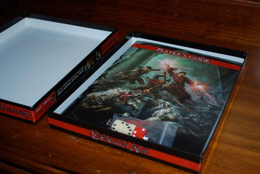 Opening the boxed reveals a thin players guide booklet as well as a plastic bag containing three six sided dice (two white, one red).