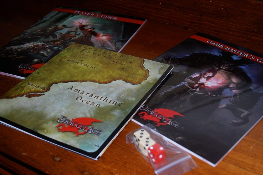 Two game booklets, a folded map, and a plastic bag containing two white six sided dice and one red die.