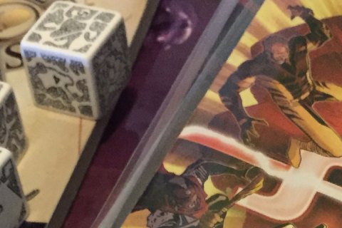 Oversized dice with dungeon maps on them sit atop an RPG manual. Nearby is a stack of comic books.