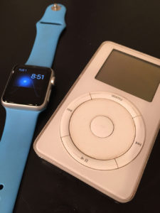 An Apple Watch next to an original iPod (rev 2)