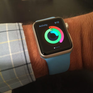 A close-up view of the apple watch displaying the three concentric circles of the activity app.