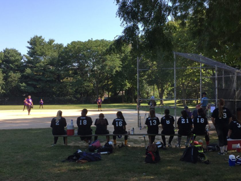 A girls' softball team watches while one of their teammate's bats.