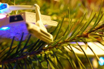 A close up shot of a starship ornament in an evergreen tree. Another starship, blurry in appearance, is in the background.