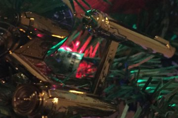 A golden starship reflects nearby Christmas lights as it hangs on an artificial tree.