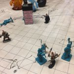 Heroes battle monsters in the foreground, while elemental figurines (representing water, fire, and earth) appear in the distance.