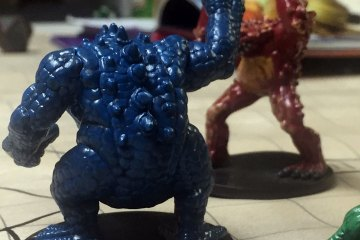 Plastic miniatures of the frog-like monsters known as slaadi stand on a battlemap. In the background can be seen several figures representing player characters.