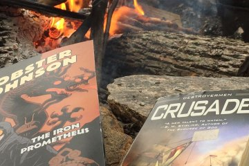 Two books -- Lobster Johnson and Crusade -- rest on rocks next to a fire pit. A fire can be seen burning in the upper portion of the photograph.