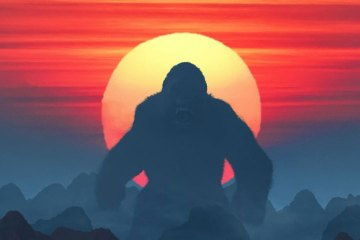 Helicopters fly toward a giant ape. The ape is backlit by a sunset; small mountains appear at his feet.