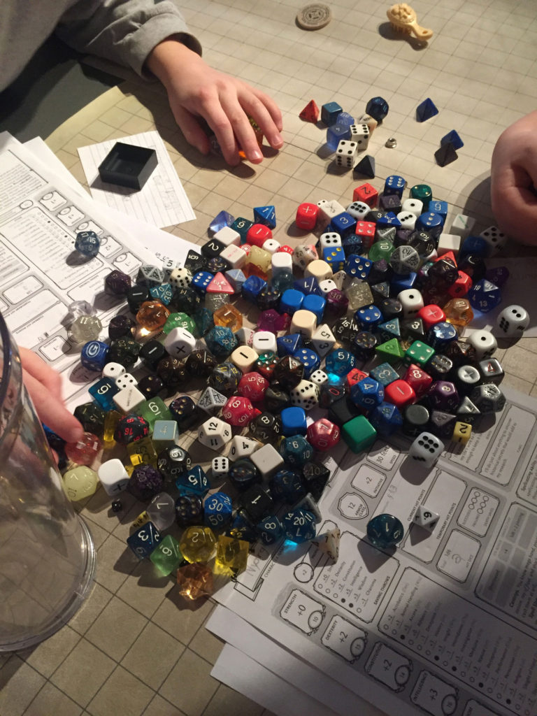 A huge pile of dice fills the picture, overflowing onto character sheets. Boys' hands reach in select dice to use in a game.
