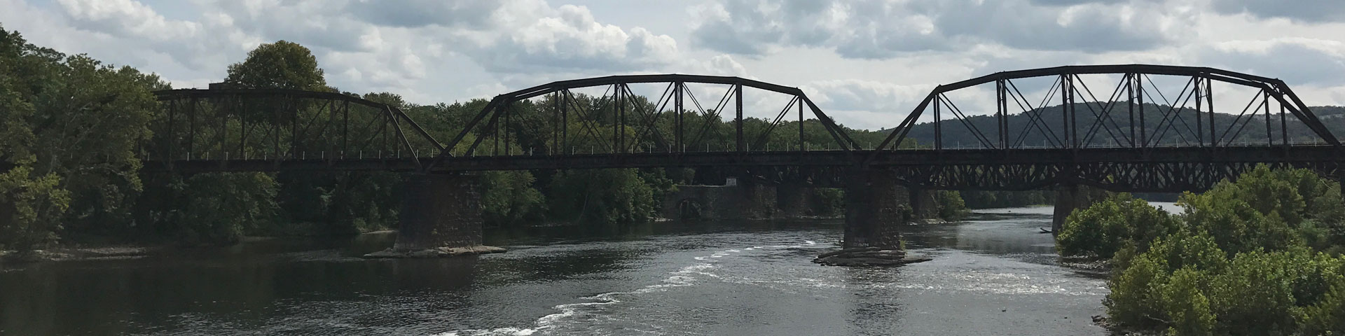 A large steel railroad bridge crosses a river.