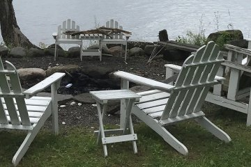 Adirondack chairs gathered around a firepit near a lake.