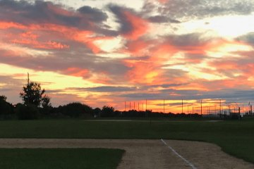 A beautiful sunset filled with tinges of orange, red, and yellow. A baseball field appears in the foreground; a large tree is silhouetted off to the right in the background