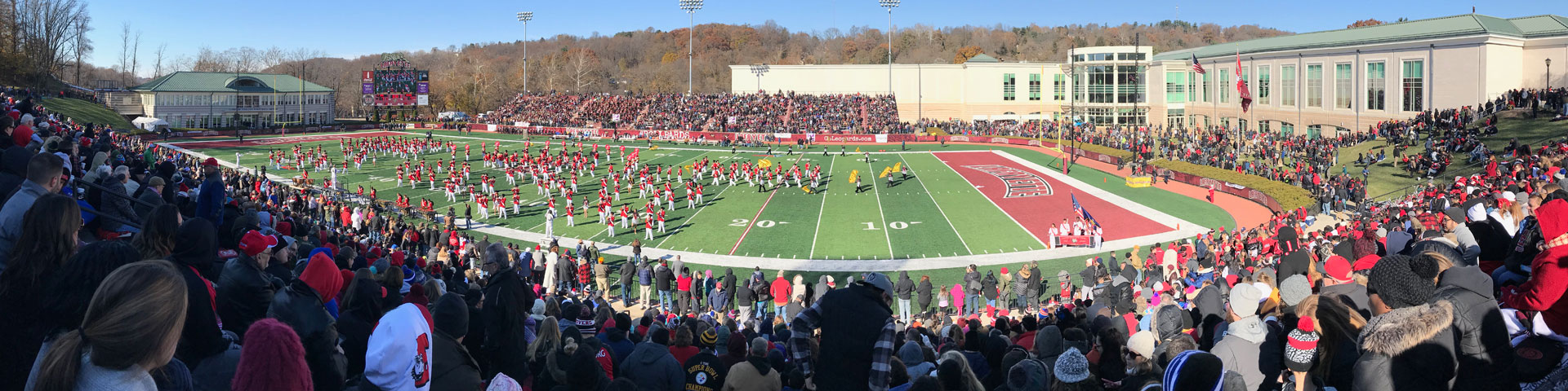 A panoramic view of a football stadium packed with people. A band in red, black, and white uniforms performs on the field.