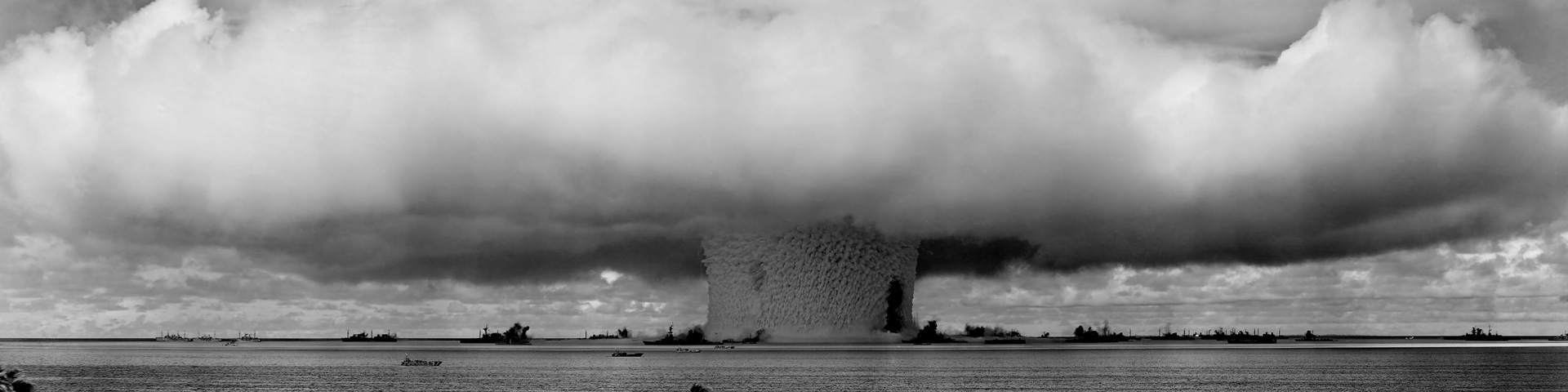 A nuclear blast at sea. Palm trees can be seen in the foreground, while ships appear in the mid-ground. The blast looms over all.