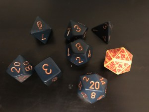 A set of dice for D&D. There are 7 blue dice with gold numbering, and one yellow die with red lettering.