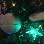 The sphere of the Death Star appears to the left; the starship Enterprise to the right. A glowing blue star is seen beneath them.