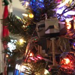 The Apollo-era Lunar Lander nestled among Christmas lights on an evergreen tree.