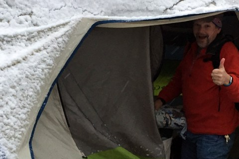 A middle-aged man (Ken Newquist) gives the thumbs up from a snow covered tent