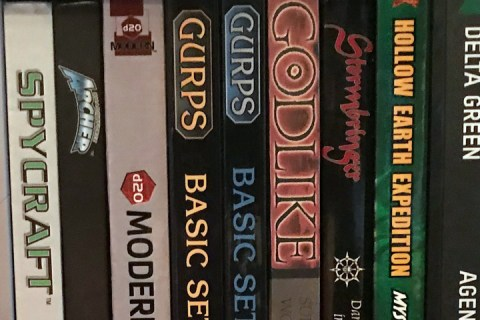 A close up view of the spines of numerous role-playing game books.