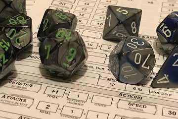 A close up view of dice sitting on a pair of character sheets.