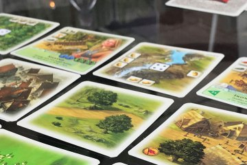 Cards representing cities, forests, mountains, fields, and other regions are laid out on a glass table.