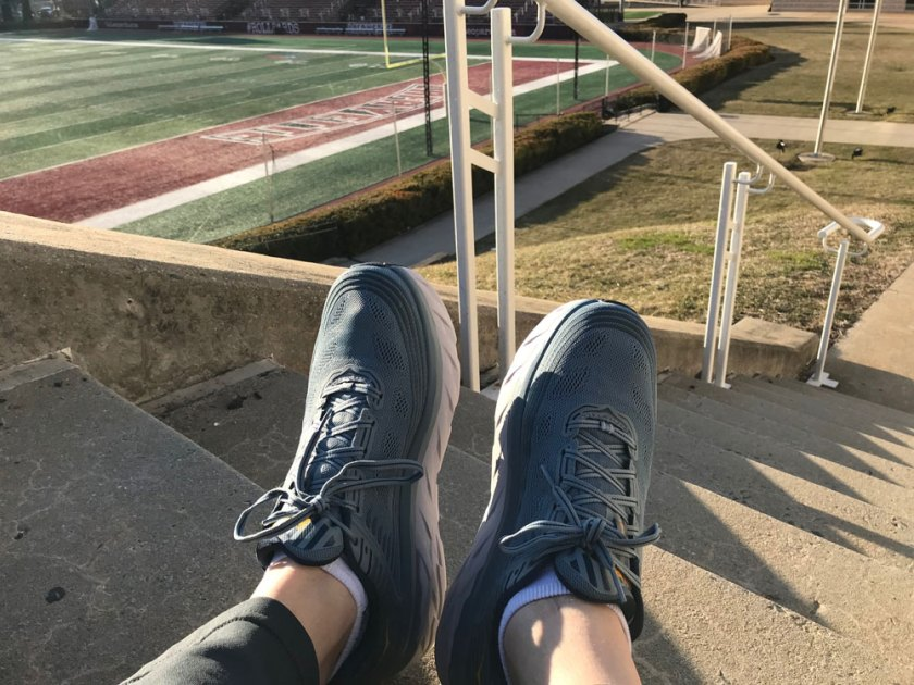 A photo of grey sneakers taken on a staircase. A football field appears in the background.