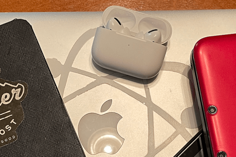 A variety of electronic devices including a Kindle Paperwhite, Airpods, Nintendo Switch, Nintendo 3DS, and a MacBook Pro laptop