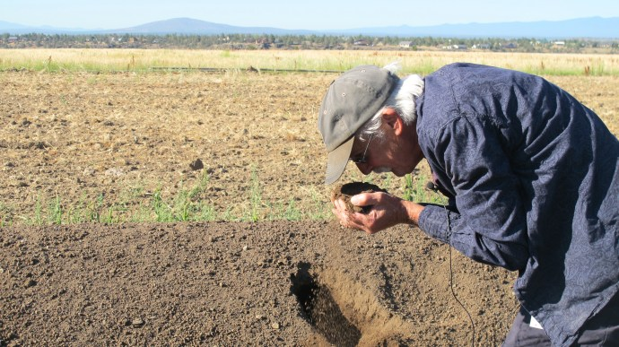 Randy smelling dirt at Oregon's Wild Harvest