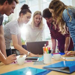 workshop - piati mladí ľudia nad pracovným stolom