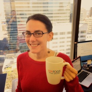 Gina Helfrich, Communications Director. Brunette woman with black wire frame glasses, smiling and holding a coffee cup that reads