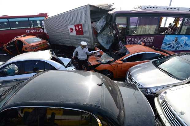 A policeman walks between damaged vehicles on Yeongjong Bridge in Incheon