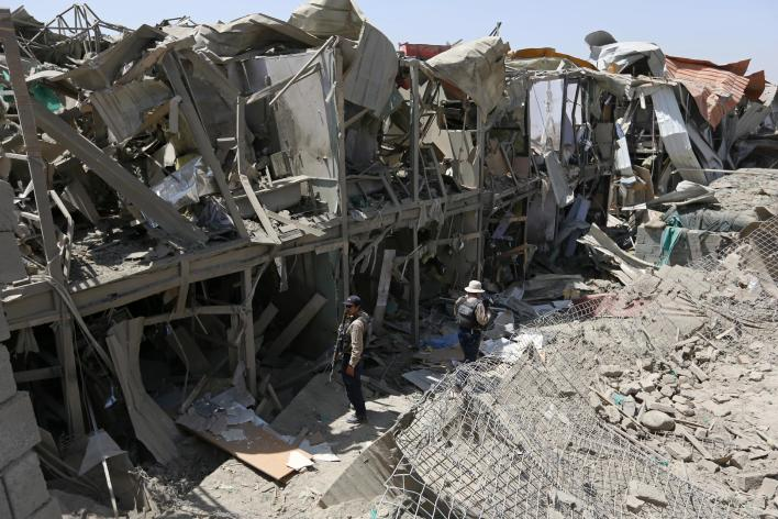 """Security guard inspect the site of a truck bombing, in Kabul, Afghanistan, Monday, Aug. 1, 2016. Afghan authorities say an overnight attack on a guesthouse for foreign contractors claimed by the Taliban has killed one policeman and wounded four others. The Interior Ministry says """"terrorists"""" used a truck full of explosives to breach the wall of the hotel around 1:30 a.m., then three gunmen entered the premises and started shooting. (AP Photos/Rahmat Gul)"""