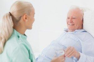 Elderly man in nursing home with caregiver