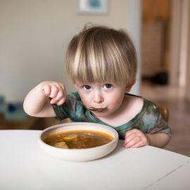 little boy enjoying soup