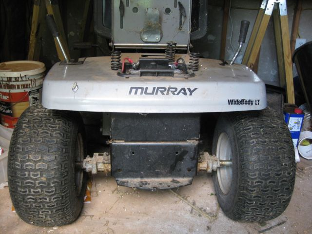 view of rear of lawn tractor showing rear wheel, transaxle and below upraised seat, the battery housing