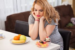 Pregnant young woman trying to decide whether to eat fruits or sweets, sitting at the kitchen table