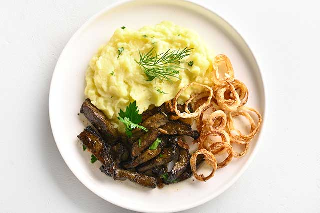 Fried Beef Liver, Onions, and Mashed Potato On a White Plate.