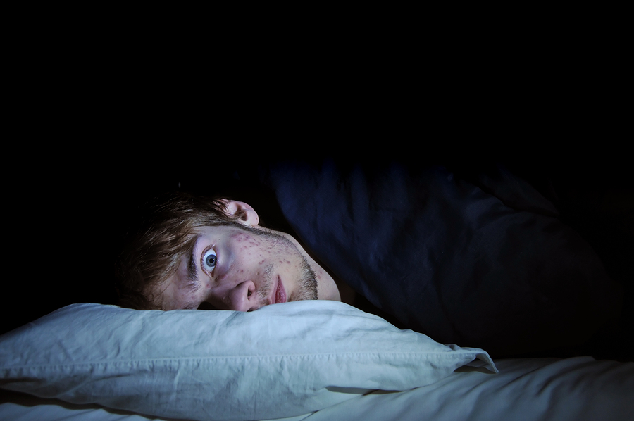 Man with insomnia stares pop-eyed at camera, head on pillow.